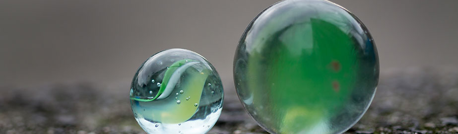 Two green marbles on concrete surface
