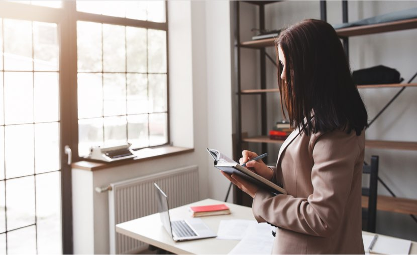 woman-taking -notes-in-office