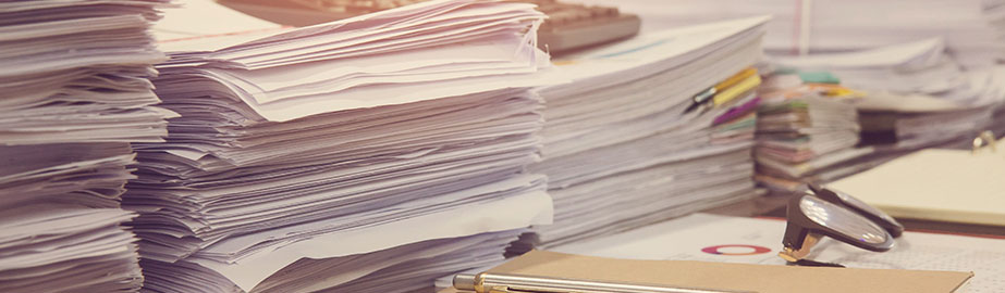 Piles of papers on desk with glasses