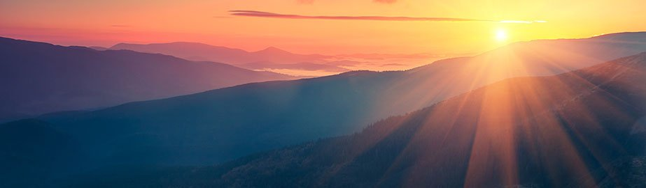Sunrise over blue mountains with sunbeams