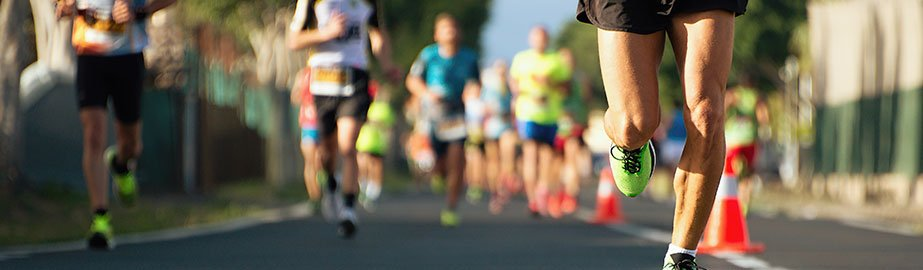 Runner taking lead in race on road with many other contestants following