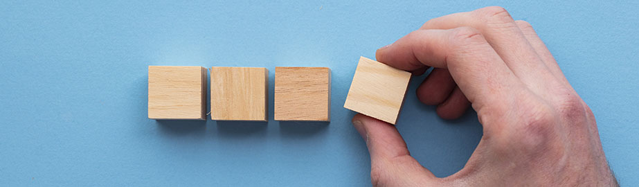 Hand chooses one of four wooden blocks from blue background