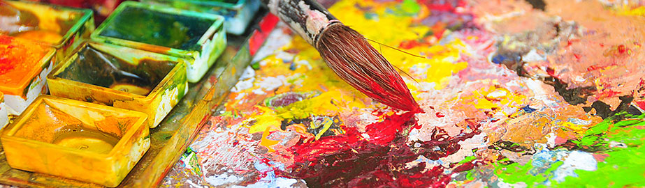 Paintbrush and brightly colored wet paints on artist's canvas