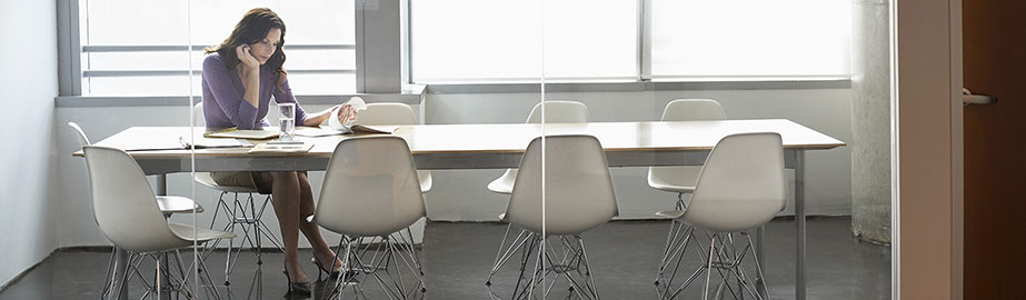 Businesswoman sitting alone in conference room with large windows.