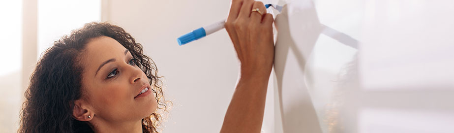 Woman writing on whiteboard with blue dry-erase marker